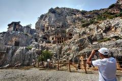 Tourists take pictures Rock-cut tombs ancient town Myra, Antalya Stock Image
