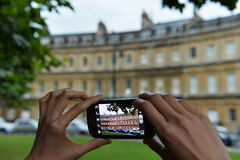 Tourists Takes a Photo with a Smartphone. A tourist uses a smartphone to capture a local landmark on August 9, 2014 in Bath, UK. A popular travel destination and Royalty Free Stock Images
