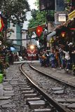 Tourists taking photo of train on tracks running very narrow to houses in Hanoi stock photo