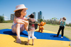 Tourists taking photograph of large model doll and bear. Royalty Free Stock Images