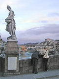 Tourists taking photos. Two tourists taking photos from a bridge in Florence - Italy, at dusk, with an ancient statue over their heads Stock Photos