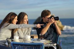 Tourists taking photos from a coffee shop. Three happy tourists taking photos from a coffee shop on the beach on vacation royalty free stock images
