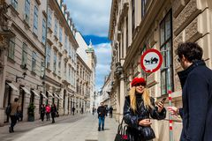 Tourists taking pictues at a beautiful street on Vienna inner city with a horse-drawn Vehicles likely to be in road sign. VIENNA, AUSTRIA - APRIL, 2018: Tourists royalty free stock photos