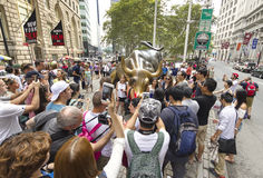Tourists taking pictures of the Charging Bull. Stock Image