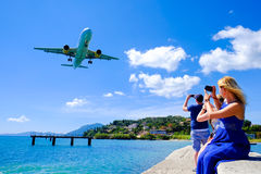 Tourists taking pictures in Corfu. Plane landing stock photography
