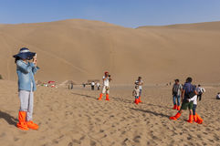 Tourists taking pictures in the dunes around the city of Dunhuang, in the ancient Silk Road, in China. Stock Photo
