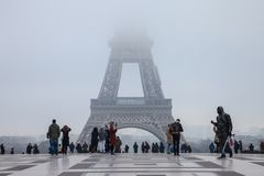 Tourists taking pictures in front of the Eiffel Tower, the top of the tower hidden by clouds and fog due to bad weather. Picture of the Eiffel tower whose top is royalty free stock photography