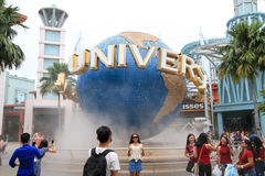 Tourists taking pictures in front of Universal Studios Sentosa island. SINGAPORE - JULY 9, 2017 : Tourists taking pictures in front of Universal Studios Sentosa Royalty Free Stock Photography