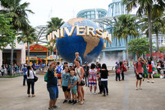 Tourists taking pictures in front of Universal Studios Sentosa island. SINGAPORE - JULY 9, 2017 : Tourists taking pictures in front of Universal Studios Sentosa Stock Photos