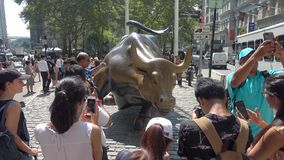 Tourists are taking pictures with a very famous bull sculpture on the Broadway.