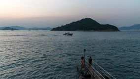 Tourists taking pictures at western swimming shed in the sunset. Hong Kong stock video footage