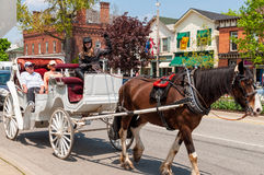 Tourists taking a ride in a horse carriage. Two seniors taking a ride in a horse carriage on Queen street, the main shopping street in Niagara On The Lake royalty free stock photo