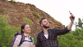Tourists taking selfie on background of mountains. Two tourists with backpacks on the back taking selfie on a phone on a background of mountains stock footage