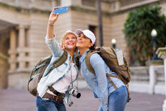 Tourists taking selfie. Happy female tourists taking a selfie with smart phone Royalty Free Stock Images
