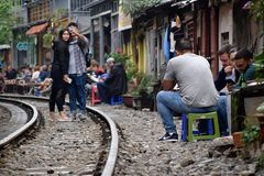 Tourists on and next to the railway tracks running narrow next to houses in Hanoi stock photos