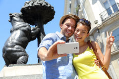 Tourists taking selfie photo by bear statue Madrid. Tourists taking selfie photo pictures by famous bear statue Madrid on Puerta del Sol. Young couple using Royalty Free Stock Images