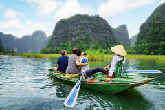 Tourists taking selfie. Rower using her feet to propel oars. Tourists traveling in boat along the Ngo Dong River and taking selfie at the Tam Coc, Ninh Binh Royalty Free Stock Images