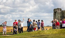 Tourists taking selfies in front of Stonehenge in Wiltshire, UK. On 13 August 2016 royalty free stock image
