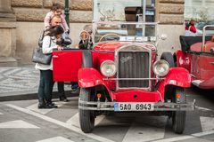 Tourists talk with a driver of red oldtimer car. Prague, Czech Republic - May 2, 2017: Tourists talk with a driver of red vintage oldtimer car on the street of Stock Photography
