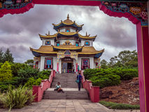 Tourists at the temple. Buddhist temple with tourists in Gramado - Tres Coracoes - Brazil, the red and gold contrasts with the grey clouds in the sky Royalty Free Stock Image
