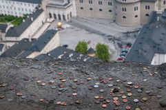 Tourists throw many lucky coins to the balcony of Salzburg fortress. Stock Photos