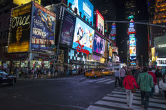 Tourists at Times Square at night, the famous location in New York city, full of people and cars and its neon light signs. Stock Photography