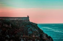 Tourists in the top of a cliff admiring the view of the horizon and the ocean royalty free stock image