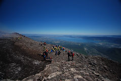 Tourists on top of volcano Stock Images