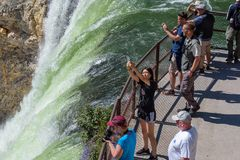 YELLOWSTONE NATIONAL PARK, WYOMING, USA - JULY 17, 2017: Tourists and a tour guide watching Lower Yellowstone Falls. Grand Canyon. Tourists and a tour guide Royalty Free Stock Photo