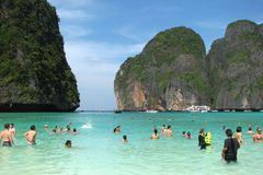 Tourists and tourist boats on the famous beach in Maya Bay on one of the islands of Phi Phi, Thailand stock image