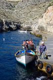 Blue Grotto departure point, Malta. Tourists in traditional Dghajsa water taxi boats at the departure point in the bay, Blue Grotto, Malta, Europe Royalty Free Stock Image