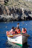 Tourists with bouyancy aids at Blue Grotto, Malta. Tourists in traditional Dghajsa water taxi boats at the departure point in the bay, Blue Grotto, Malta Stock Photos