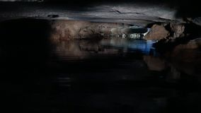 Boats traveling through the caves. Tourists in traditional local boats traveling through the caves and grottoes of the limestone mountains at Van Long Nature stock video footage