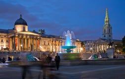 Tourists on Trafalgar Square. Tourists visiting Trafalgar Square in early evening Royalty Free Stock Photo
