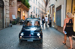 Tourists and traffic on the narrow street in Rome, Italy. Royalty Free Stock Photography