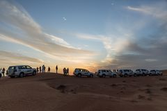 Tourists with travel cars parking for see the sun down in the evening in the great desert at Dubai Stock Photo