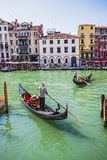 Tourists travel on gondolas at canal Stock Photos