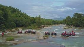 Tourists Travel on Quadricycles across Tropical River Rapids. HON BA/VIETNAM - AUGUST 05 2017: Aerial view tourists travel on quadricycles across river rapids stock video