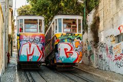 Tourists Travel By Vintage Funicular On Narrow Old Streets Of Lisbon City Royalty Free Stock Images