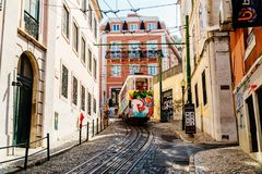 Tourists Travel By Vintage Funicular On Narrow Old Streets Of Lisbon City Royalty Free Stock Photo