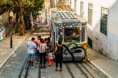 Tourists Travel By Vintage Funicular On Narrow Old Streets Of Lisbon City Stock Photography