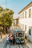 Tourists Travel By Vintage Funicular On Narrow Old Streets Of Lisbon City Stock Images