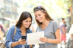 Tourists traveling consulting a phone and a guide. Two happy tourists traveling consulting a smart phone and a paper guide in the street Stock Photos