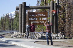 Tourists Traveling Visting Grand Teton National Park. A family tourist taking a picture in front of the sign for the Grand Teton National Park royalty free stock photography