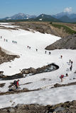 Tourists traverse mountain river on snowfield. Russia, Far East, Kamchatka Peninsula Stock Image