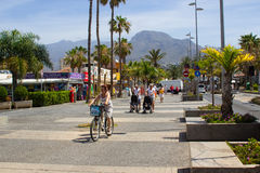 Tourists on a tree lined avenue with shops and cafes in Playa de Las Americas in the island of Teneriffe Stock Photo