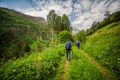 Tourists with trekking pole going on mountain Cheget Stock Images