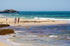 Tourists on tropical beach and ocean stock photos