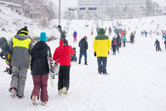 Tourists trudging through snow at a ski resort Stock Images