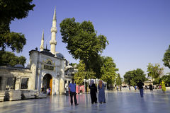 Tourists and Turkish people walking near The Eyup Sultan Mosque, square on a bright day Royalty Free Stock Photos